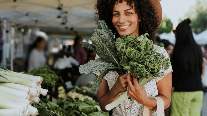 woman shopping for kale at farmer's market