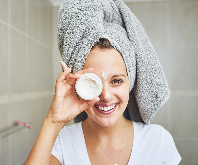 woman applying moisturiser happy
