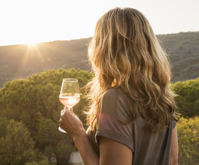 Woman holding glass of wine watching sunset over hills