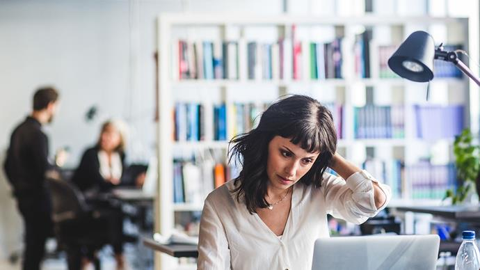 woman in an office staring at screen stressed