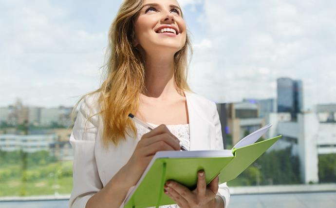 Young woman writing in notebook outside