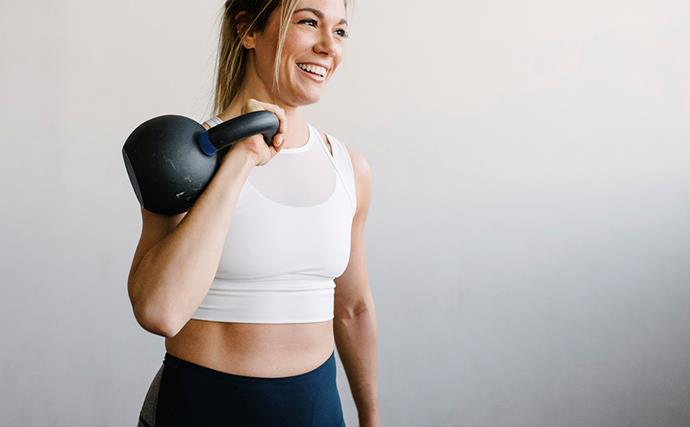 woman holding a kettle bell and smiling