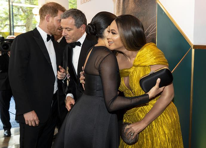 Meghan Markle and Beyonce greet each other with a hug at the premiere of The Lion King, while Prince Harry chats to Disney CEO Bob Iger. *(Image: Getty)*