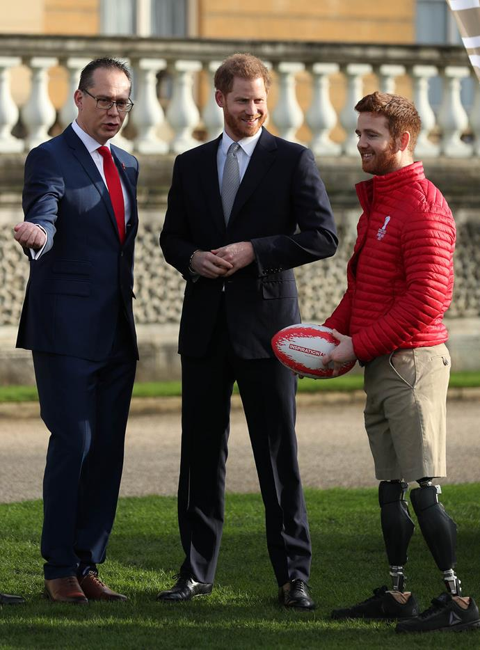 Prince Harry chats with the CEO of the Rugby World Cup Jon Dutton and Leeds Rhino player James Simpson at Buckingham Palace for the tournament's draw. *(Image: Getty)*
