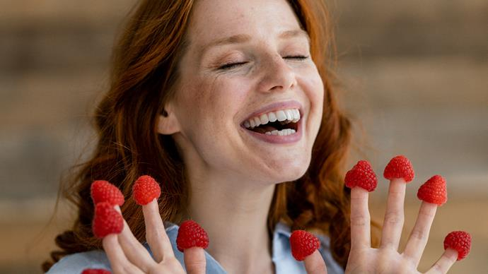 laughing redheaded woman with raspberries on her fingertips