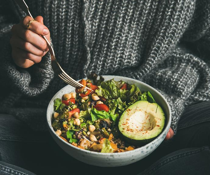 woman holding healthy buddha bowl salad
