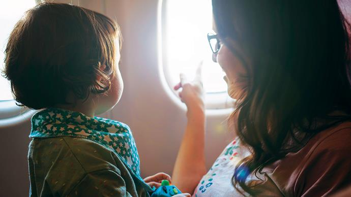 Mum and baby looking out window of plane