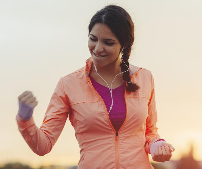 woman in exercise gear pumping fist in air