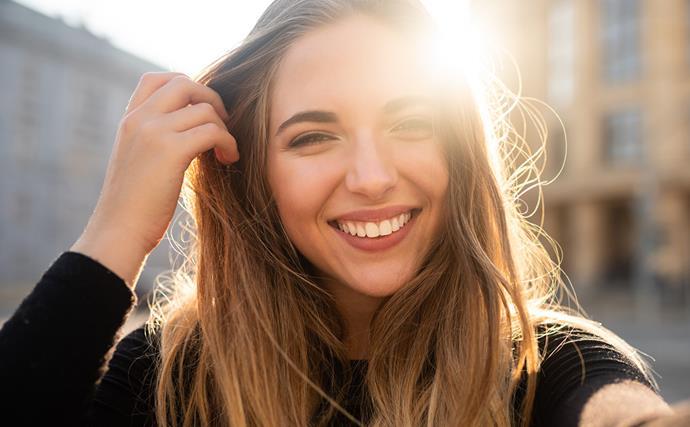 woman smiling hand through hair