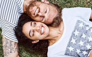 Multi-ethnic couple lying on grass at back yard