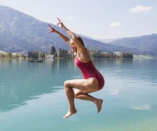 Middle aged woman in red swimsuit jumping into lake