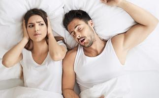 Couple in bed, man snoring woman wide awake