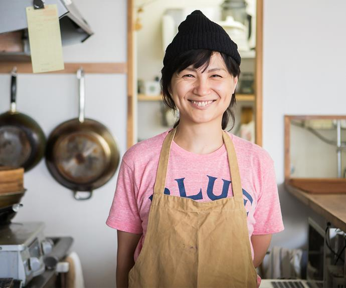 woman business owner stands proudly in the kitchen of her shop