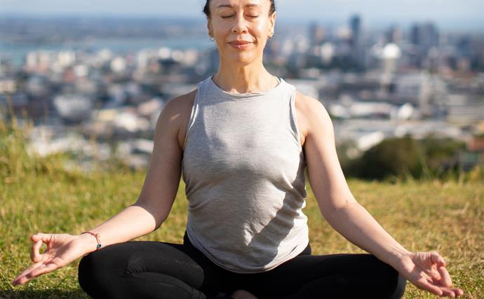Woman doing yoga on top of Maungawhau Mt Eden