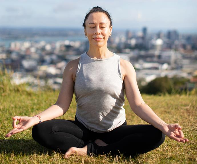 Woman doing yoga on top of Maungawhau Mt Eden