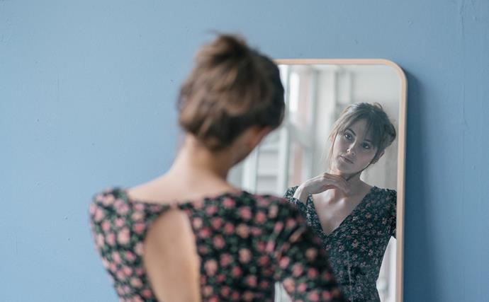 Indecisive woman looking in mirror