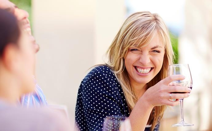 woman smiling and drinking wine