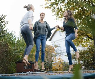 Three women bouncing on trmapoline