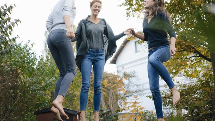 Three women bouncing on trmapoline