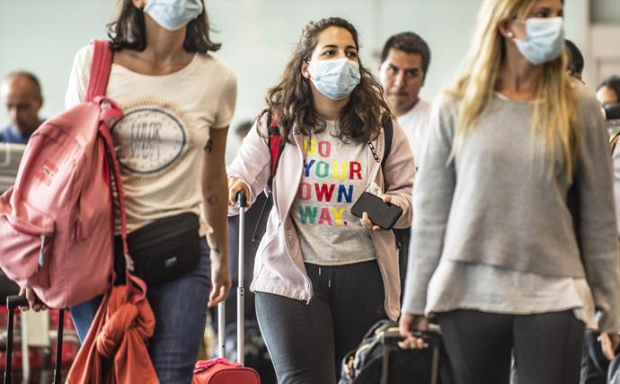 Girls walking through airport wearing face masks