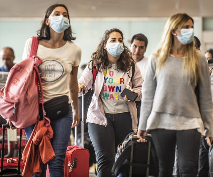 Girls walking through airport wearing face masks