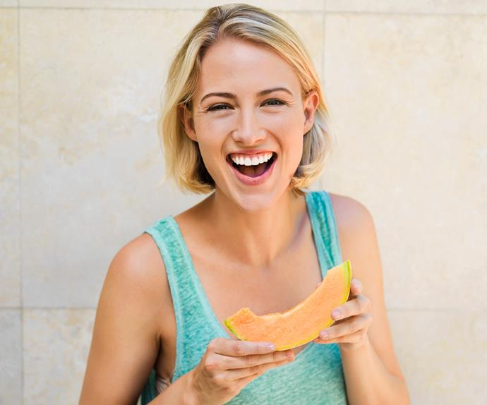 smiling woman eating melon