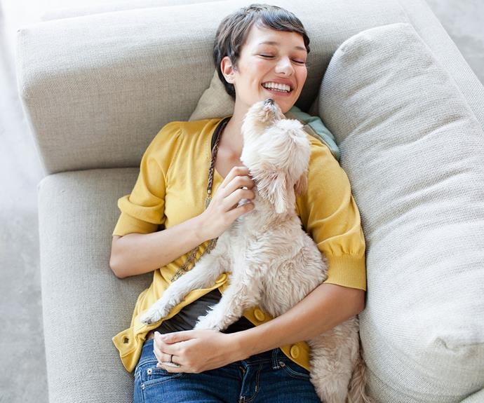 woman hugging a dog on her sofa