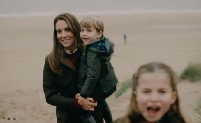 Duchess Catherine carries Prince Louis on the beach as a cheeky Princess Charlotte makes an appearance. (Image: Will War/Kensington Palace)