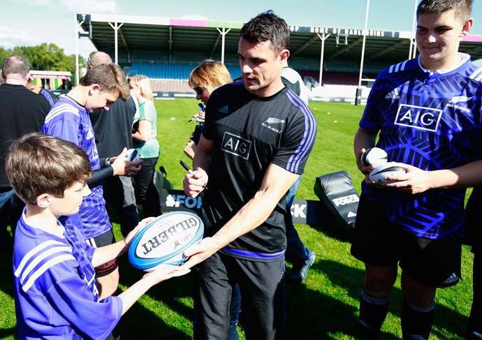 **September 2015**: Dan signs a rugby ball for a young fan during an adidas event at Twickenham Stoop in London. Photo: Getty