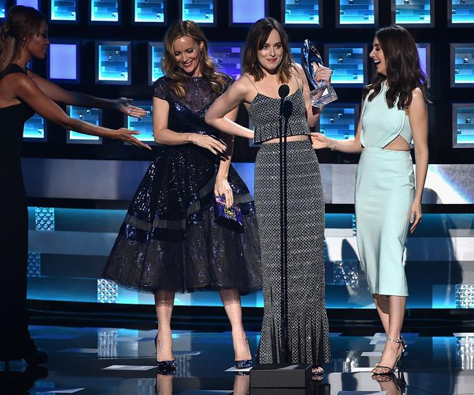 Leslie Mann helps Dakota Johnson on stage at the People's Choice Awards. Photo: Getty