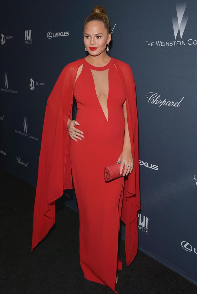**February 27, 2016:** Lady in red! The model looked stunning in a Michael Kors gown that featured a subtle cape detail and a plunging neckline.