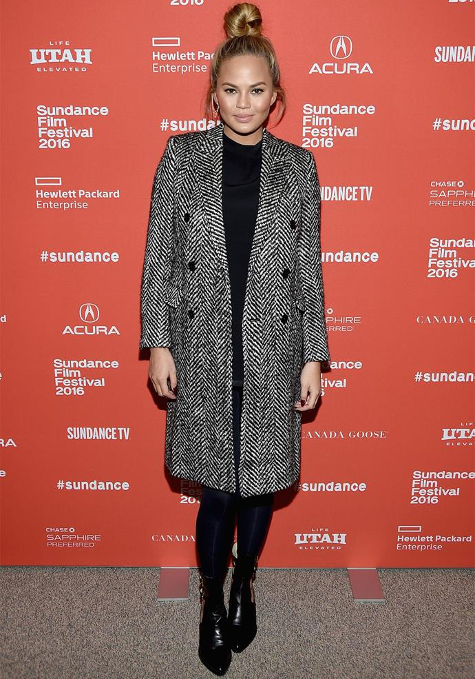**January 24, 2016:** Dressed warmly for the cold weather, Chrissy pairs an all-black ensemble with a stylish grey peacoat.