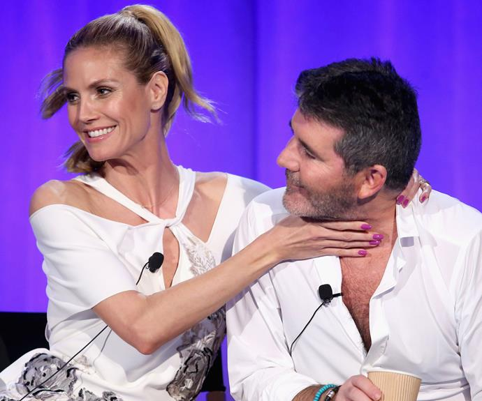 Heidi Klum is all smiles as she gets Simon Cowell in her grip. Photo: Getty