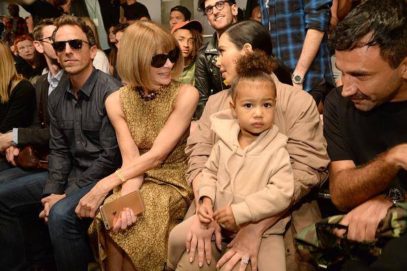 North matches her mum as Kim chats to *Vogue's* Anna Wintour at a fashion show.
