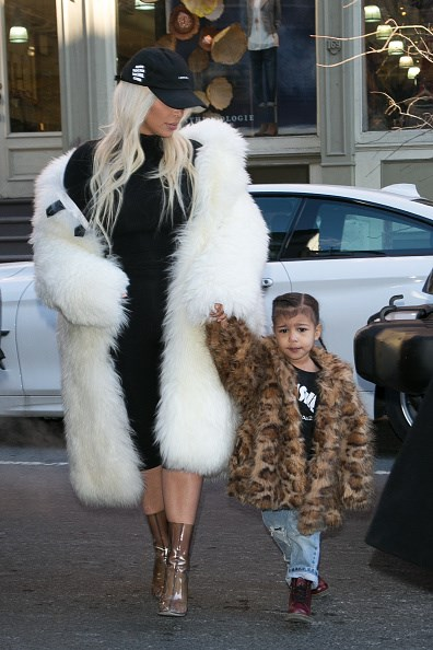 Taking a walk on the wild side! North dabbles in animal print while mum Kim Kardashian West opts for an eye-cataching white coat.