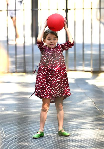 Suri shows off her sporty side in a vibrant patterned dress and green shoes.