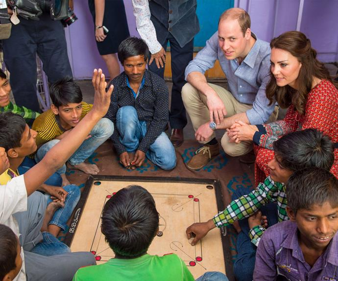 Playtime continued as Prince William and the  Duchess of Cambridge play a game of carrom with street children.