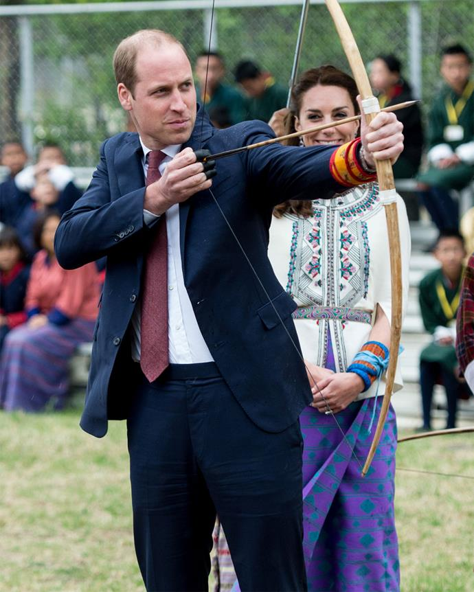William tries his hand at the bow and arrow as Kate looks on.