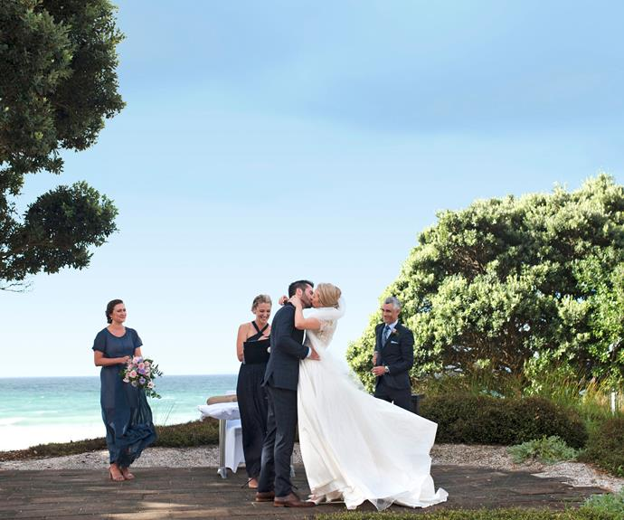 The newlyweds share a kiss as the sun breaks through.