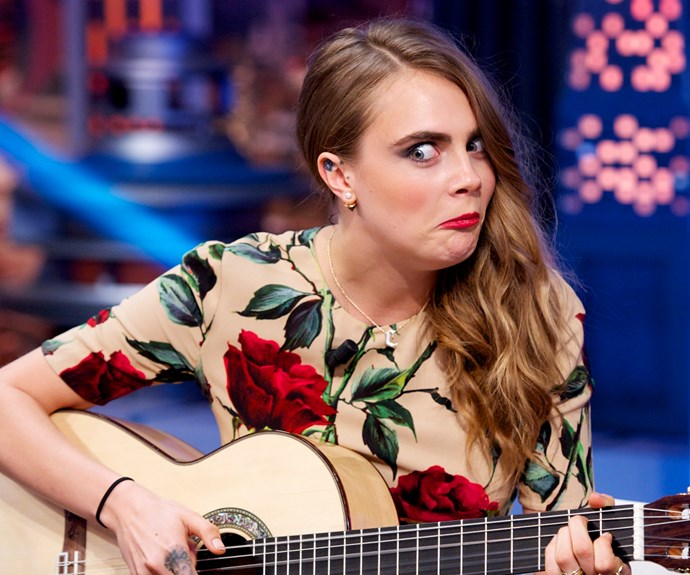 Cara Delevingne pulls a face while showing off her impressive guitar skills.