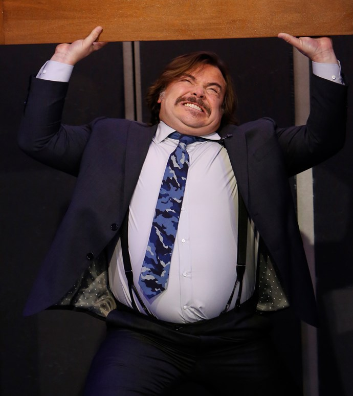 Jack Black grits his teeth as he struggles to lift a wooden beam.