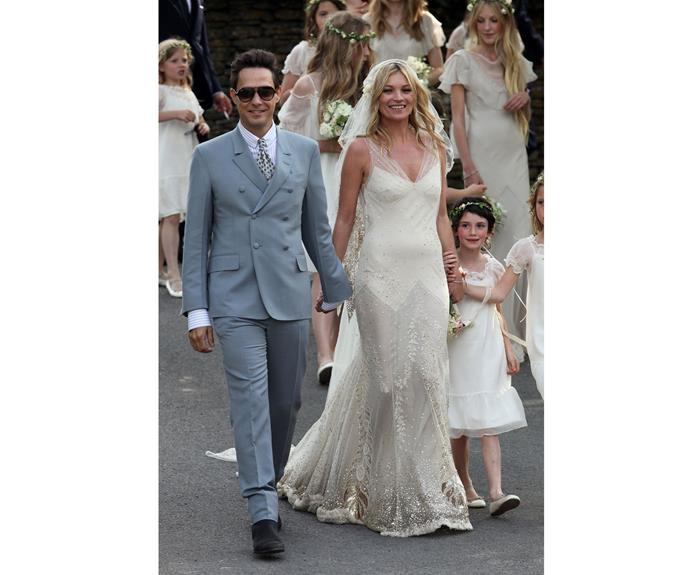 Kate Moss and Jamie Hince smile as they walk outside the church after getting married on July 1, 2011 in Southrop, England.