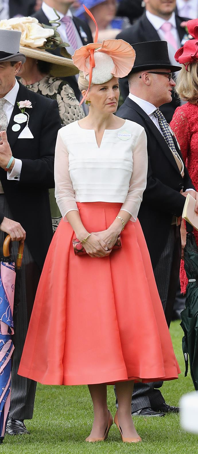 Sophie, Countess of Wessex, cut a bright figure on the racecourse in her coral and white ensemble by British designer Suzannah.