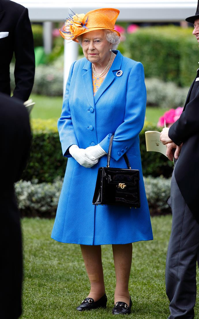 The royal completed her look with a chic black handbag, white gloves, a bejewelled brooch and three strands of pearls.