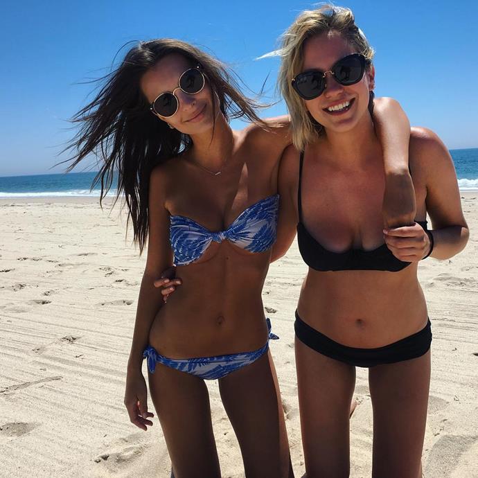 Model Emily Ratajkowski showed off her trim figure in a tiny bikini as she posed beachside with a gal pal.