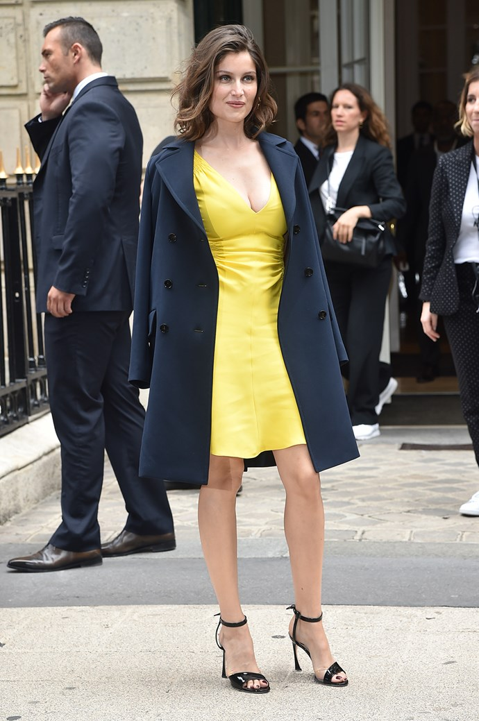 Model Laetitia Casta showed off her endless legs in a sunny yellow mini dress at the Dior show during Paris Fashion Week.
