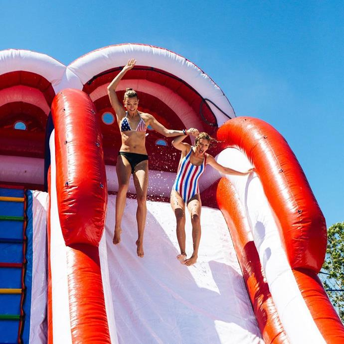 The singer and her model BFF Karlie Kloss take a ride down the giant inflatable slide Taylor had installed at her house for the party.