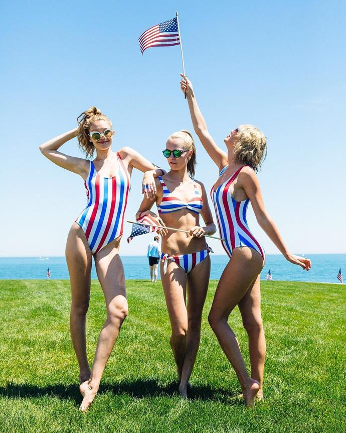 Gigi Hadid, Cara Delevingne and Taylor pose in matching swimsuits on the lawn.
