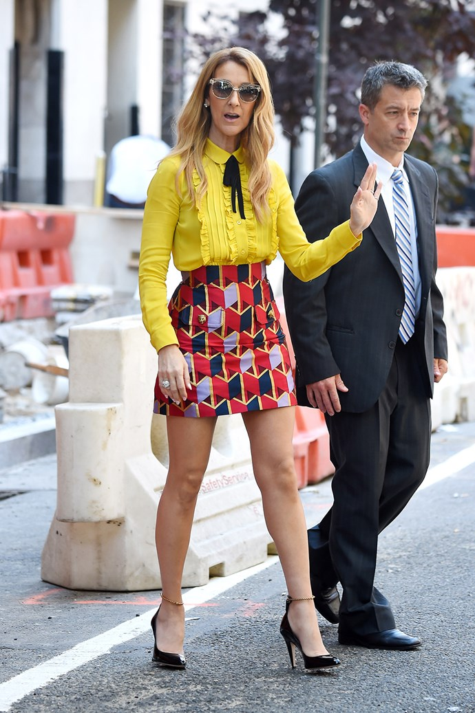 Celine Dion wows in an elegant mustard-yellow blouse paired with a contrasting patterned mini-skirt as she steps out in New York's Upper East Side.