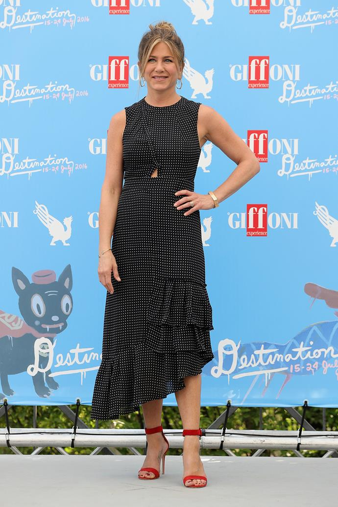 Jennifer Aniston wows in a ruffled dress with an asymmetrical hem at the Giffoni Film Festival in Italy.  **Watch the actress give a candid answer to a jury member at the festival in the video - gallery continues after**